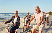Active senior tourist friends bike riding along ocean