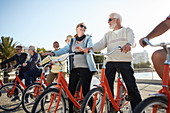 Active senior tourist friends bike riding on sunny boardwalk