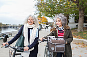 Active senior women friends walking bicycles in autumn park