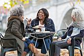Laughing active senior women friends sharing dessert
