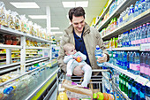 Father with baby daughter shopping in supermarket