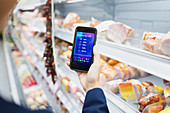 Woman using digital shopping list on camera phone
