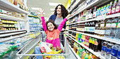 Mother pushing daughter in shopping cart in supermarket