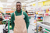 Confident male grocer working in supermarket
