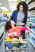 Mother pushing daughter in shopping cart in supermarket