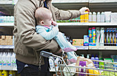 Father with baby shopping in supermarket