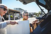 Senior women loading shopping bags into back of car