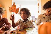 Curious boy holding autumn leaf at table