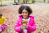 Portrait happy girl holding autumn leaf in woods