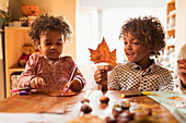 Brother and sister making crafts with autumn leaf at table