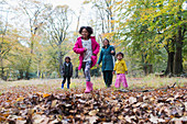 Happy family running and playing in autumn woods