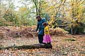 Mother and daughter walking on fallen log in autumn woods