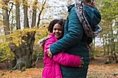 Portrait of happy girl hugging mother in autumn woods