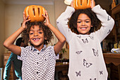 Happy brother and sister holding carved pumpkins overhead