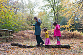 Mother and daughters balancing on fallen log in autumn woods