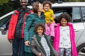 Portrait happy multiethnic family standing outside car