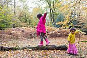 Girl walking on fallen log in autumn woods