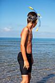 Boy wearing snorkel on beach