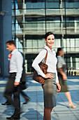 Smiling businesswoman on urban sidewalk