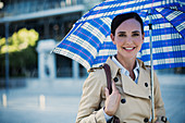 Smiling businesswoman in trench coat under umbrella