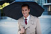 Smiling businessman in trench coat under umbrella