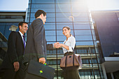 Business people shaking hands under highrise
