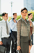 Confident businesswoman with colleagues outdoors