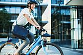 Businesswoman bike riding outside urban building
