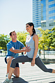 Personal trainer guiding woman with lunges in urban park