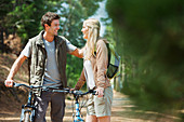 Smiling couple with mountain bikes in woods