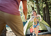 Daughter running to father outside tent in woods