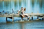 Couple on dock splashing feet in lake