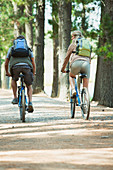 Couple mountain biking with backpacks in woods