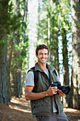 Smiling man with digital camera in woods