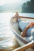 Serene man laying rowboat on calm lake