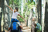 Father carrying daughter on shoulders in woods
