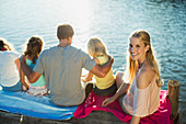 Smiling woman with family on dock over lake