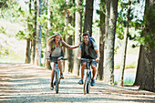 Smiling couple mountain biking in woods