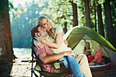 Smiling woman sitting on husbands lap at campsite in woods