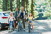 Smiling family with bicycles in woods