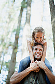 Smiling father carrying daughter on shoulders in woods
