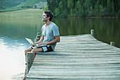 Man using laptop on dock over lake
