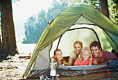 Smiling family inside of tent in woods