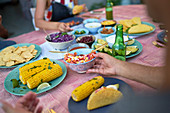 Friends eating tacos and corn at patio table