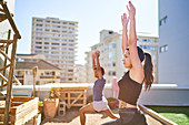 Young man and woman practicing yoga on sunny urban rooftop
