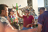 Young friends dancing and drinking beer on sunny balcony