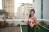 Confident young woman with smart phone and beer on rooftop