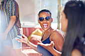 Happy young woman laughing with friends on sunny patio