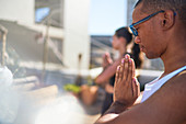 Serene young man practicing yoga on sunny patio