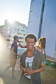 Happy young man drinking beer on sunny urban rooftop